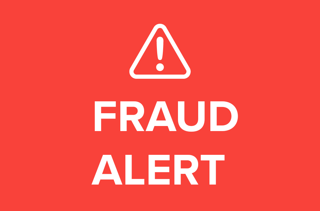 Warning symbol with fraud alert text on red background
